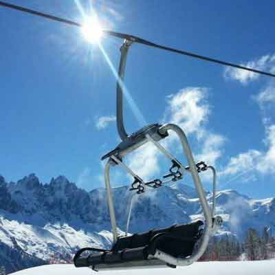 ski resort chair lift with snowy mountain backdrop