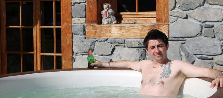 Luxury Chalets Morzine hot tub outdoor man with beer relaxing