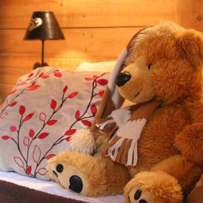 teddy sat between cushions on ski chalet bed