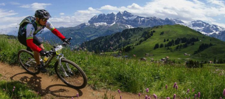 morzine summer events man riding bike with mountain scenery