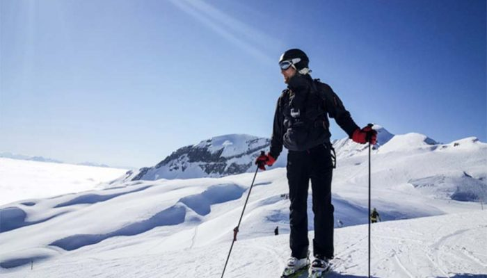 skiing in morzine at the top of a snowy mountain with blue sky